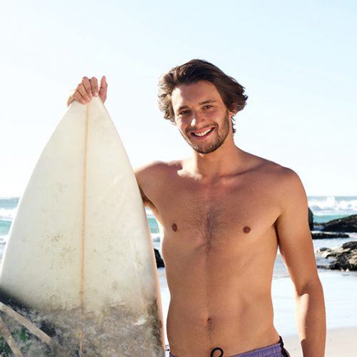 surf-guy-standing-with-surfboard-at-the-beach-P3E48SA.jpg